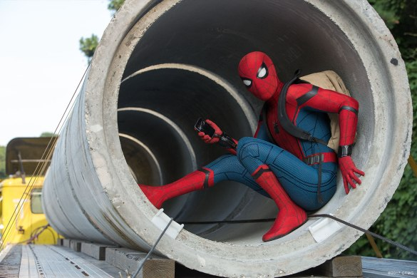 Spider-Man hiding inside a pipe with his cellphone and backpack in SPIDER-MAN HOMECOMING