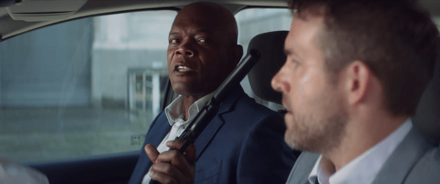 Samuel L. Jackson pointing a gun at Ryan Reynolds in THE HITMAN'S BODYGUARD.