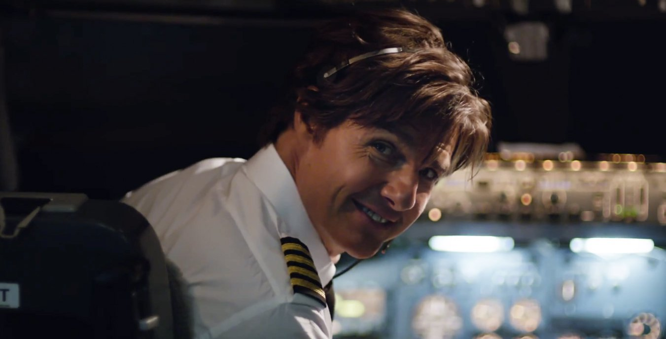 Tom Cruise in a the cockpit of a plane turning and smiling.
