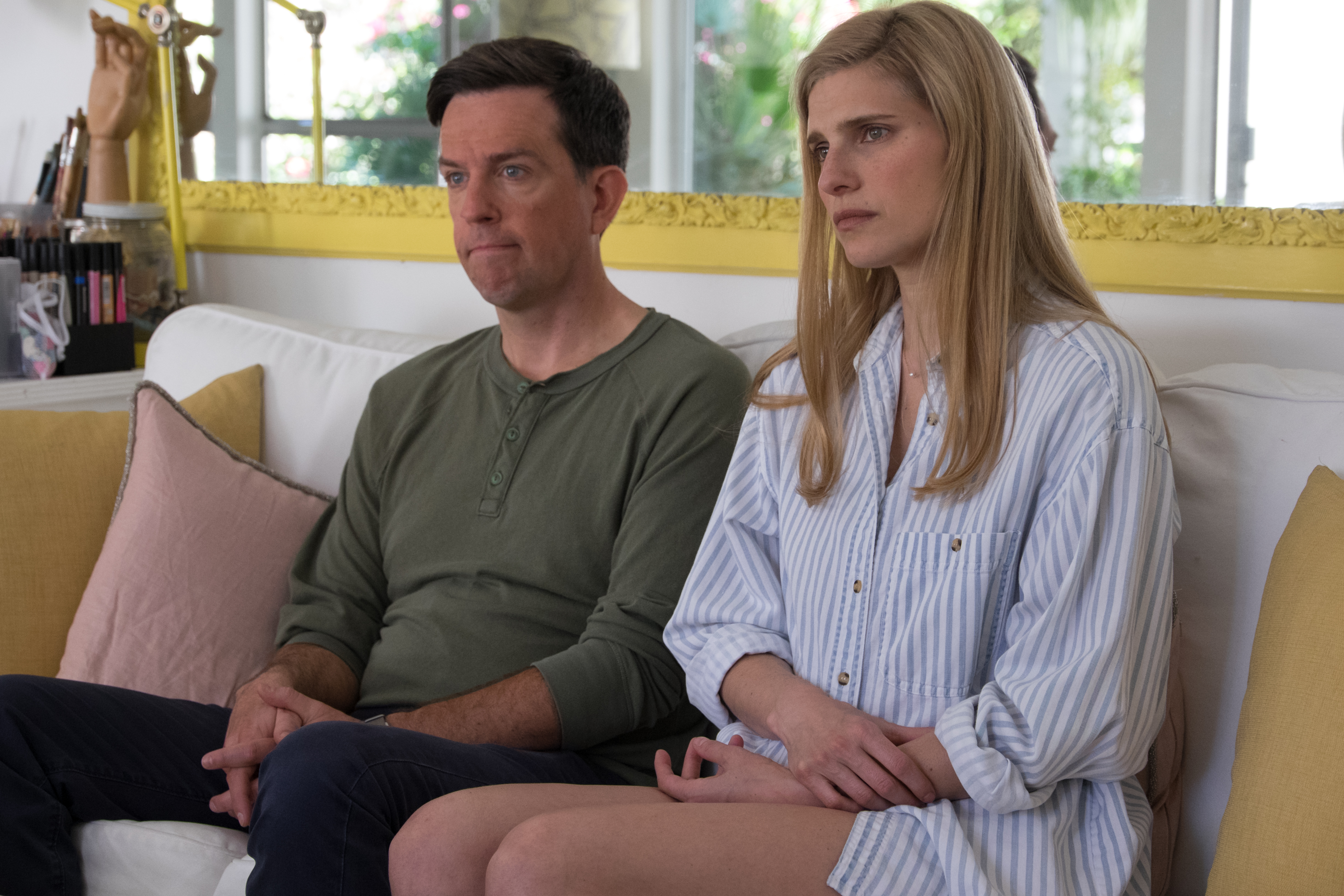 Ed Helms and Lake Bell sitting next to each other on the couch with disappointed looks in I DO...UNTIL I DON'T.