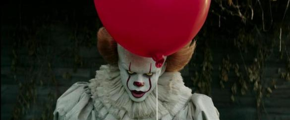 Bill Skarsgard as Pennywise in IT with a balloon near his head.
