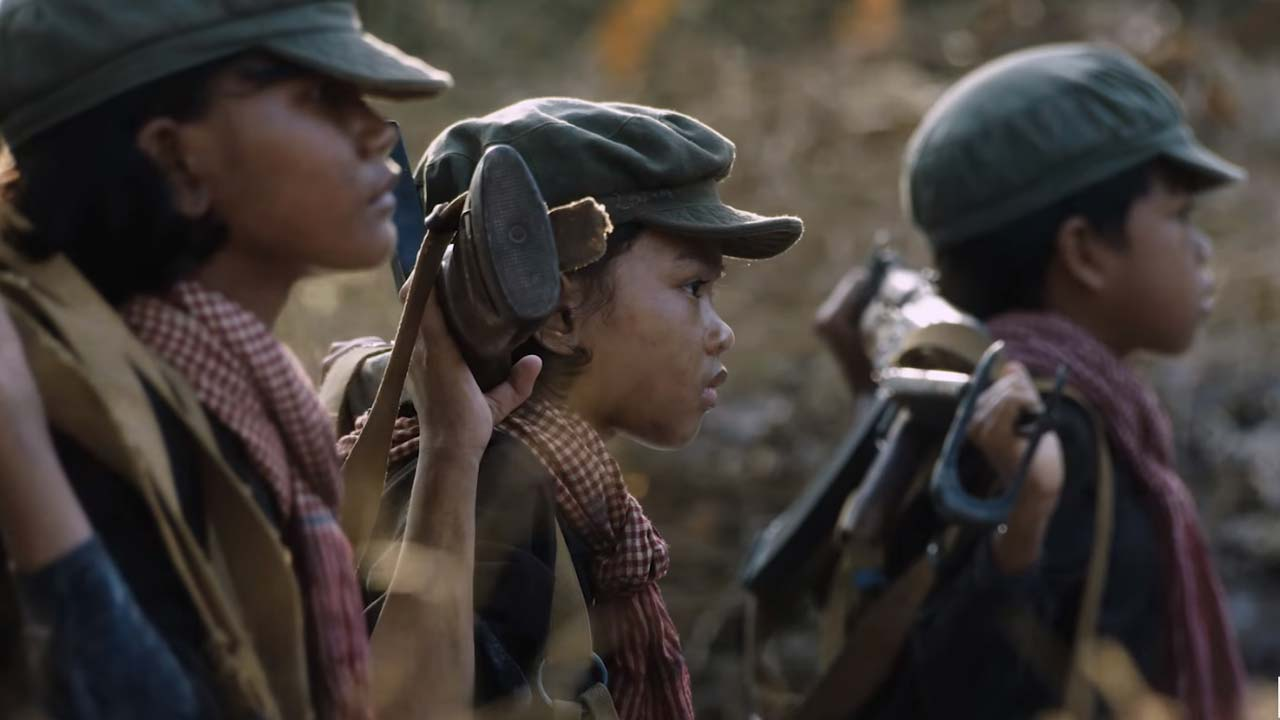 A scene of children dressed as soldiers holding guns on their backs in Angelina Jolie's film FIRST THEY KILLED MY FATHER.