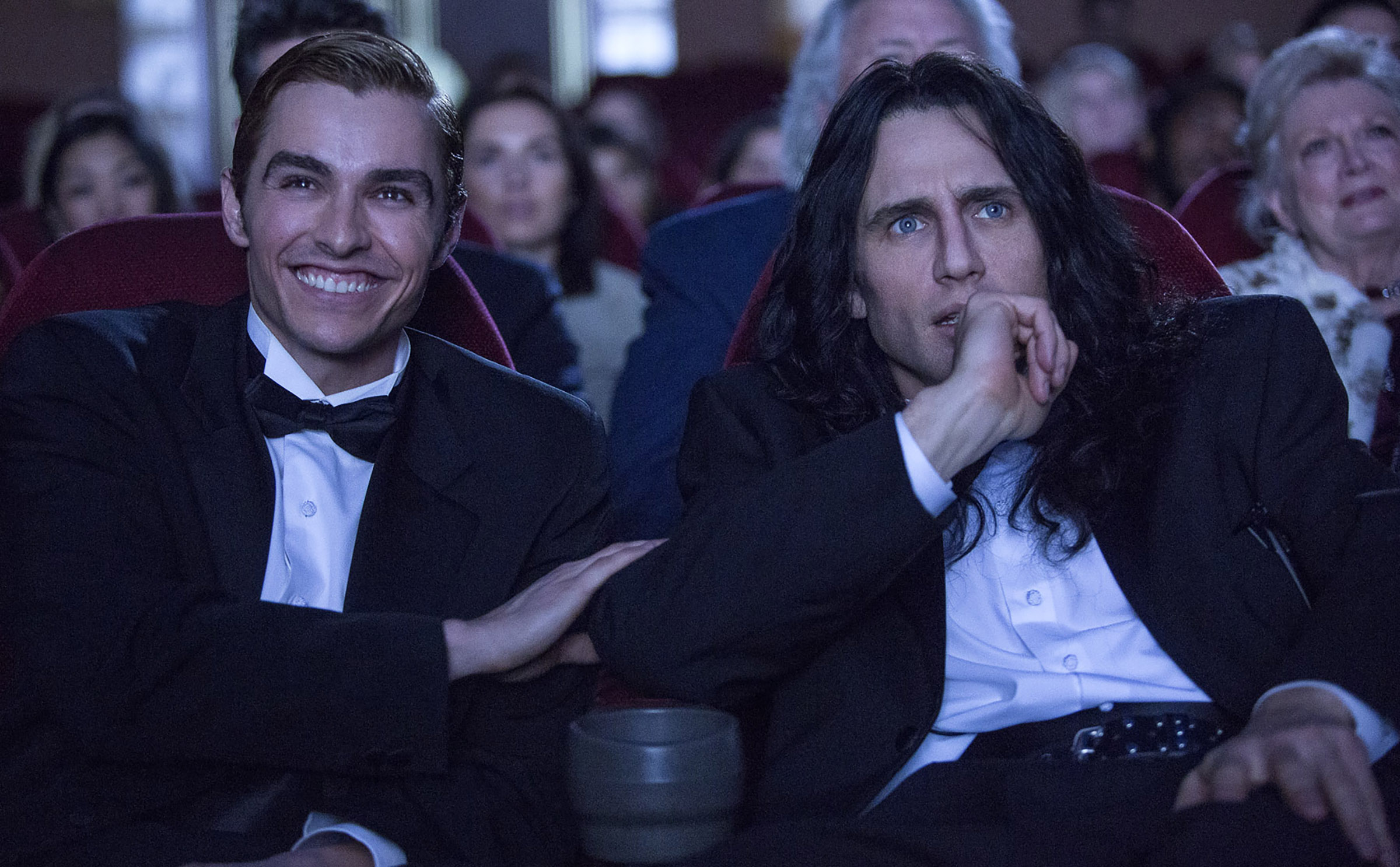 Dave Franco laughing in a movie theater with James Franco in THE DISASTER ARTIST.