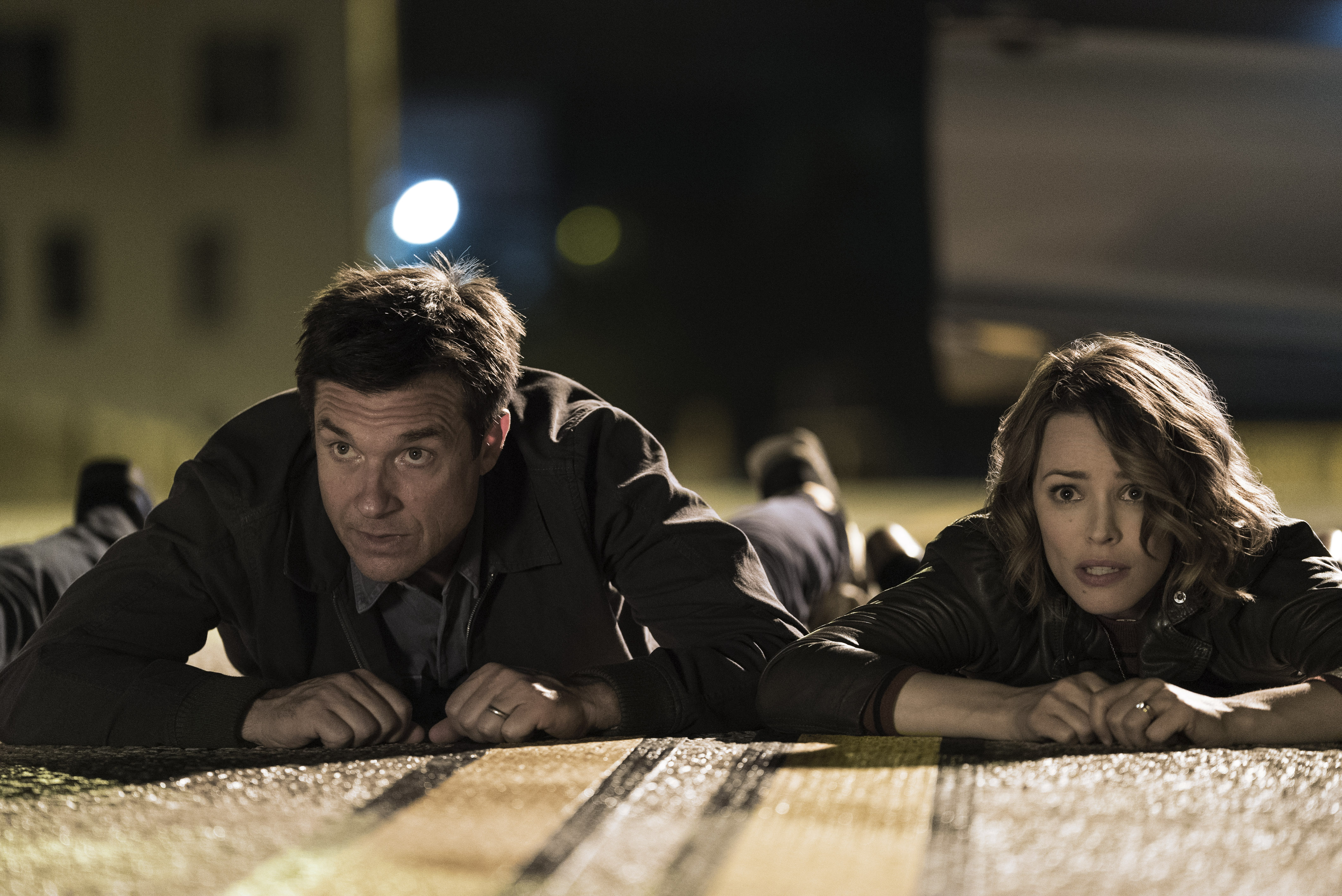 JASON BATEMAN as Max and RACHEL McADAMS as Annie lay in the middle of the street in GAME NIGHT.