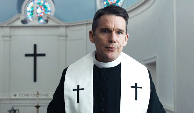 Ethan Hawke dressed as a minister in a church with his lips pursed in Paul Schrader's movie First Reformed.