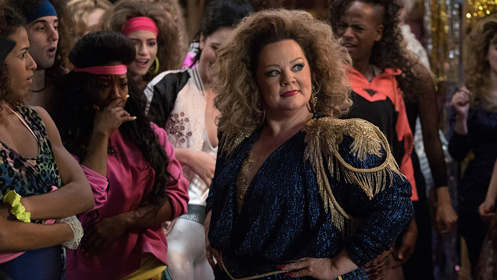 Melissa McCarthy wearing a ridiculous sparkly 80s outfit at an 80s dance off in Life of the Party.