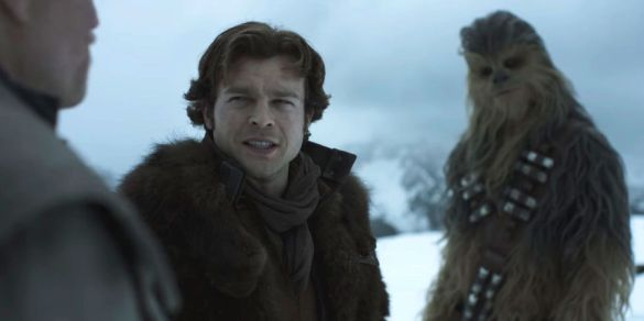 Alden Ehrenreich in Solo: A Star Wars Story looking skeptically at Woody Harrelson while Chewbacca stands in the background looking the same way with his head tilted.