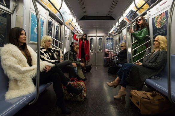 Sandra Bullock, Cate Blanchett, Rihanna, Mindy Kaling, Awkwafina, Helena Bonham Carter, Anne Hathaway, and Sarah Paulson sit on opposite sit on opposite sides of a New York subway car looking badass in Ocean's 8.