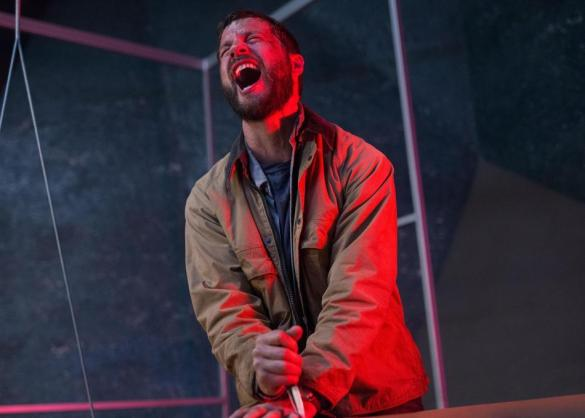 Logan Marshall-Green cries out in pain from stabbing his own hand in the sci-fi movie Upgrade.