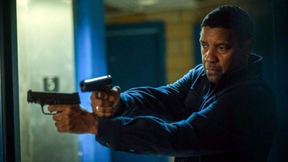Denzel Washington holding two pistols, crossing his arms and leaning around a corner in The Equalizer 2.