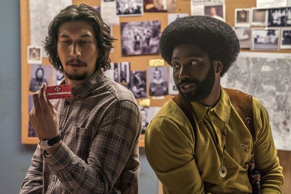 Adam Driver looks at a card from the KKK as John David Washington looks along.