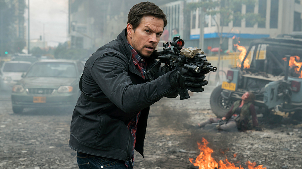 Mark Wahlberg points a gun in a tactical stance with burning cars behind him in Mile 22.