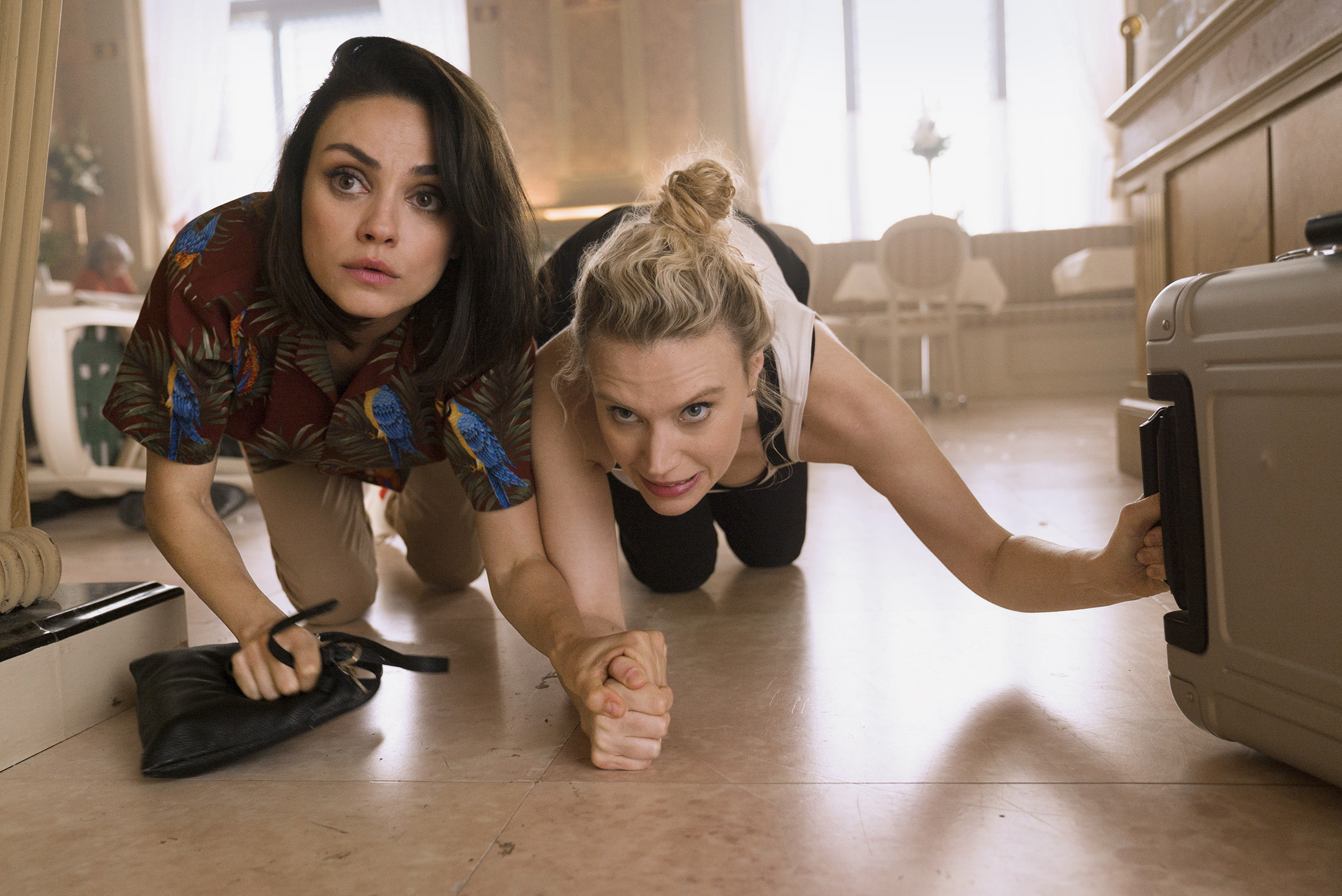 Mila Kunis and Kate McKinnon take cover on the floor with their bags in the film The Spy Who Dumped Me.