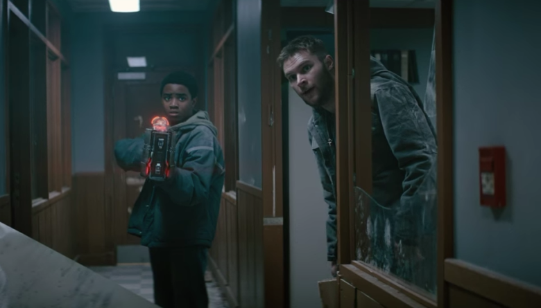 Myles Truitt aims a very big laser gun down a hallway to protect his brother played by Jack Reynor in the movie Kin