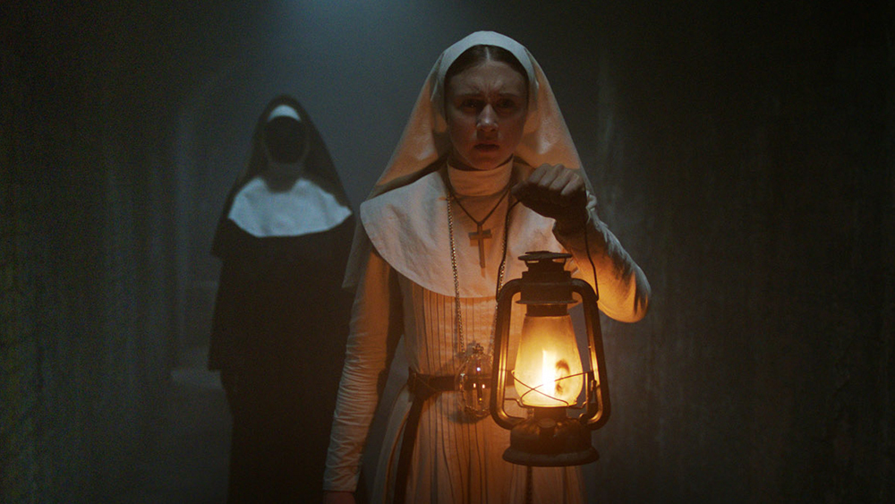 Taissa Farmiga dressed as a nun holding a lantern in a dark hallway while a ghost of anun with no face walks behind her in the movie The Nun