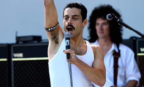 Rami Malek as Freddie Mercury in the film Bohemian Rhapsody singing at Live Aid with one arm in the air
