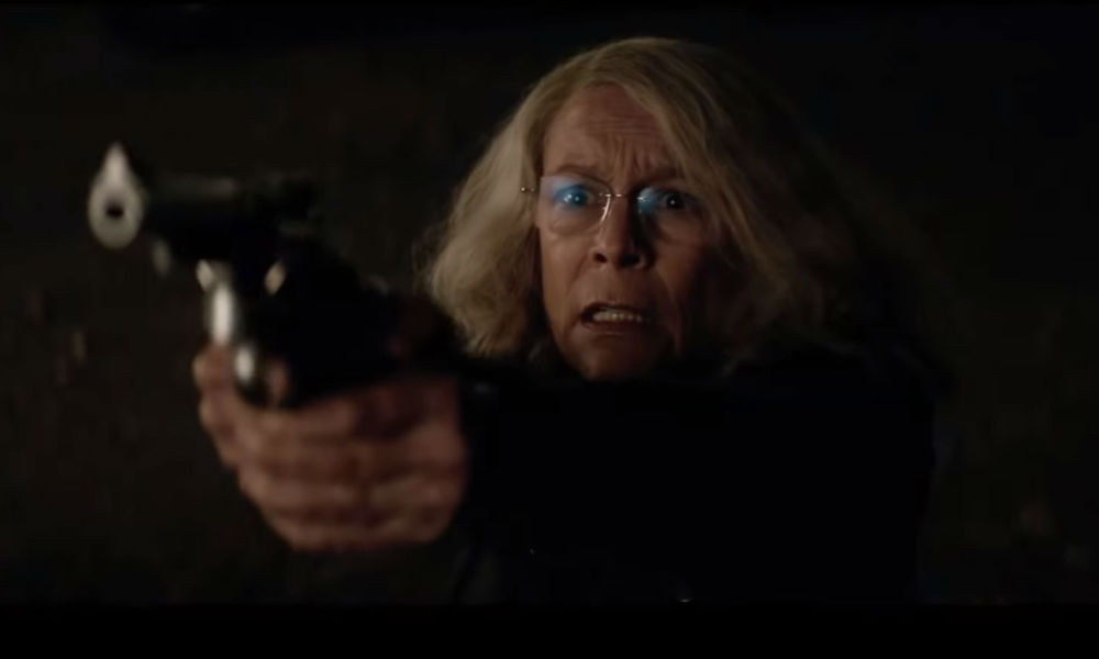 Jamie Lee Curtis looking worried pointing a revolver at the camera in the 2018 film Halloween