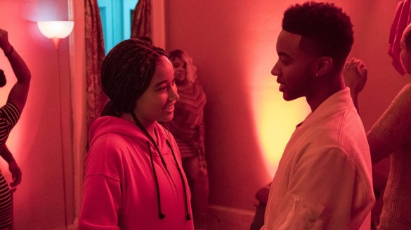 Amandla Stenberg and Algee Smith in the reddish glow of a party looking at each other and smiling in the film The Hate U Give
