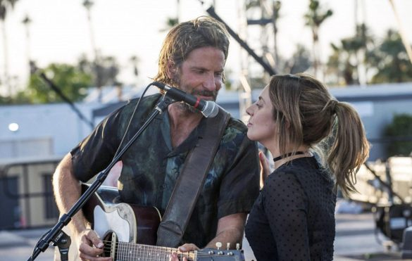 Bradley Cooper and Lady Gaga in the film A Star is Born standing next a microphone smiling and preparing to sing in front of a crowd.