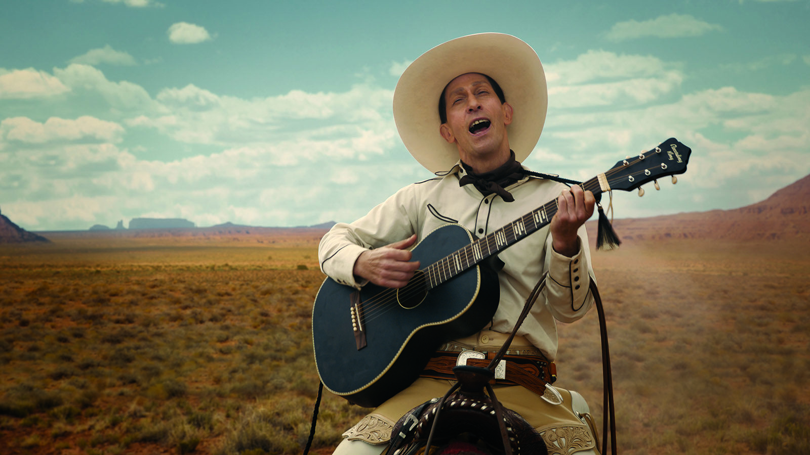 Tim Blake Nelson on a horse wearing white playing a guitar and singing in front of a picturesque landscape in the film The Ballad of Buster Scruggs