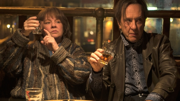 Melissa McCarthy and Richard E. Grant in the movie Can You Ever Forgive Me? are sitting at a bar holding up their glasses of liquor asking for more.