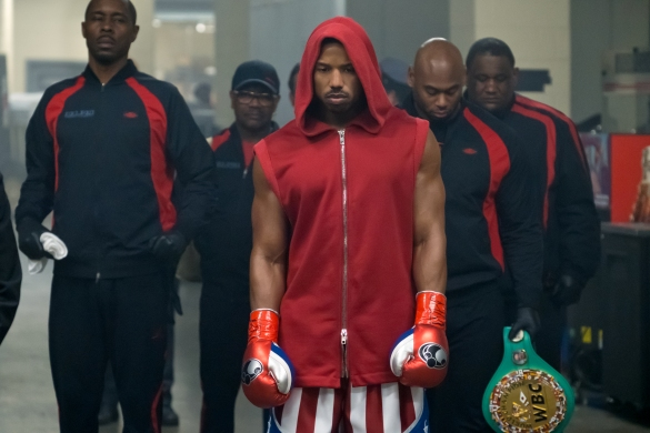 Wood Harris and a team in warmup suits escort Michael B. Jordan as Adonis Creed wearing a red boxing robe in the film Creed II.