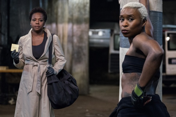 Viola Davis stands in a trenchcoat holding a Post-it note, while Cynthia Erivo stands leaning against a punching bag in workout clothes in the Steve McQueen film Widows