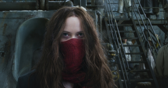 Hera Hilmar wearing a red scarf for a mask and looking intently in front of some stairs and machinery in the movie Mortal Engines