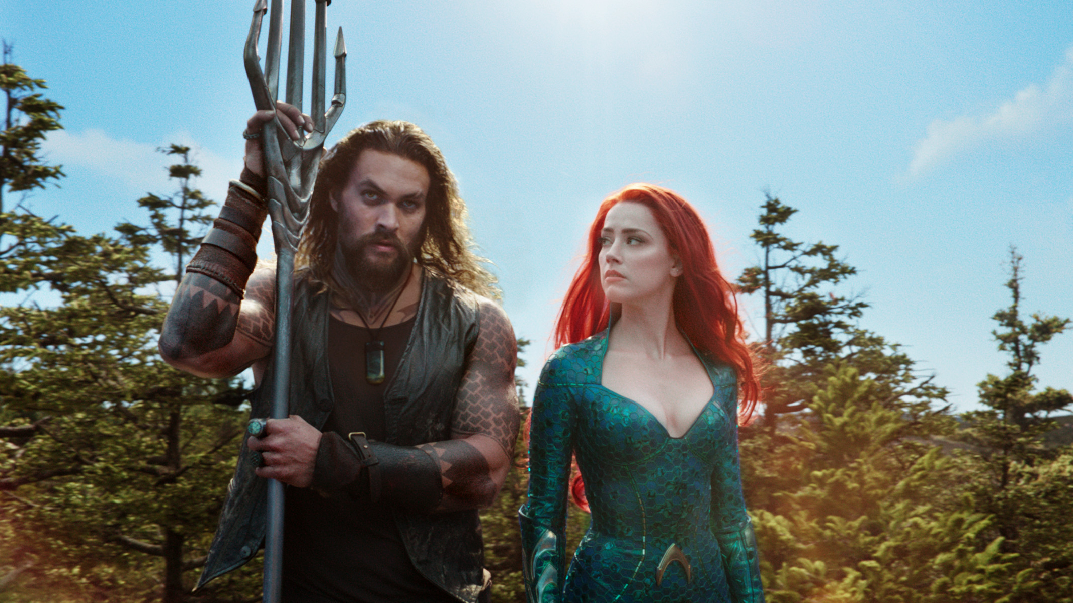 Jason Mamoa leaning on his trident and Amber Heard looking intently to him on the left in the movie Aquaman
