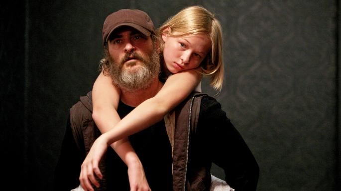 Joaquin Phoenix and carrying Ekaterina Samsonov on his back while her arms are draped over his shoulders in the movie You Were Never Really Here