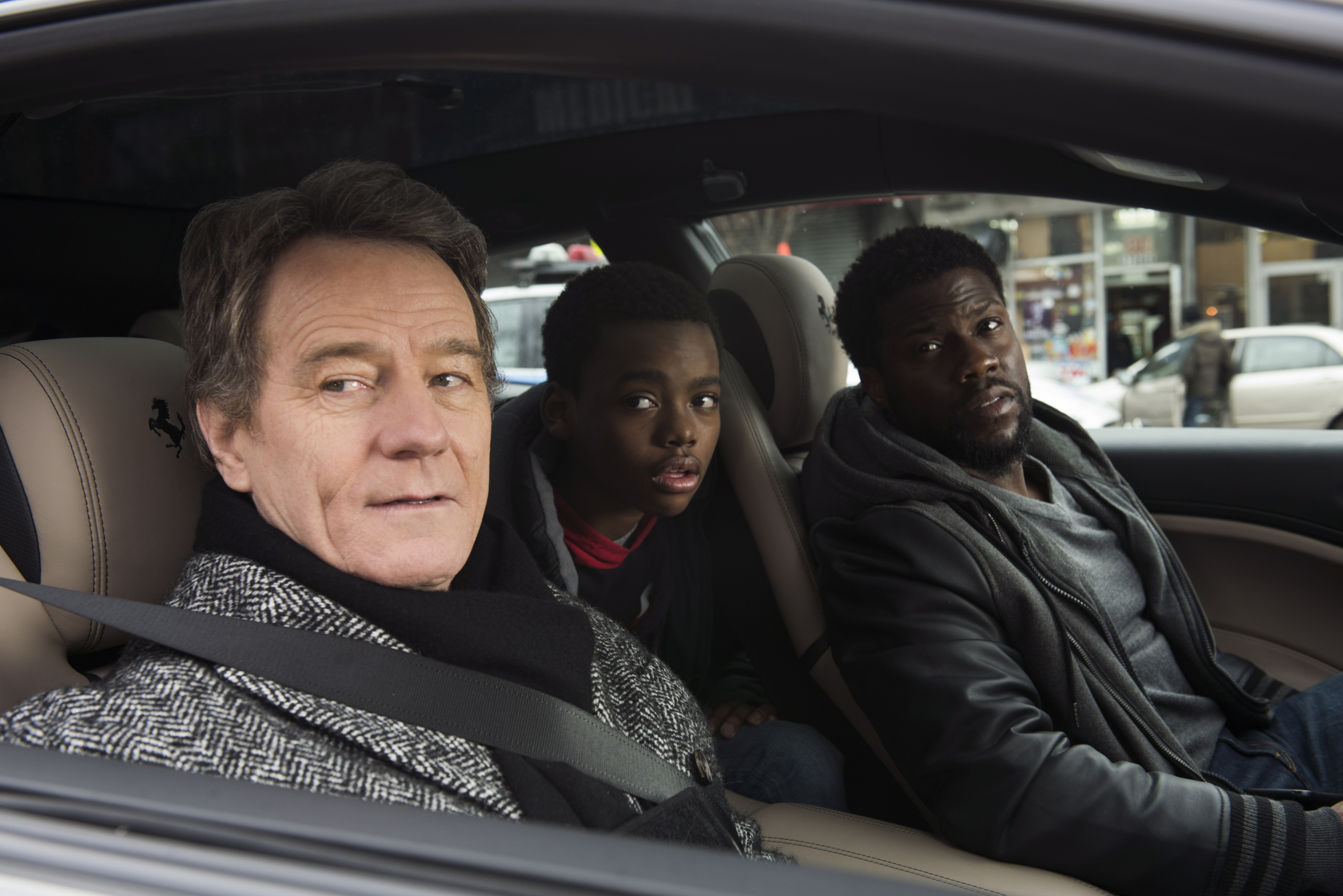 Bryan Cranston sits in the passenger seat looking out an open window with Kevin Hart in the driver's seat also looking out in the film The Upside.