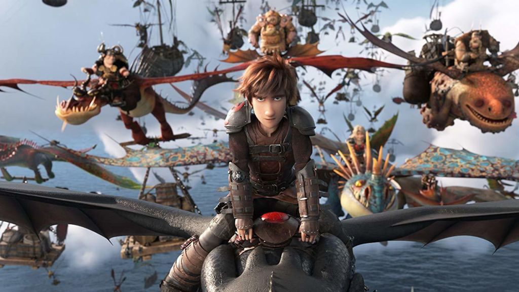 Hiccup (Jay Baruchel) rides a dragon with a fleet of dragons and riders behind him in the animated film How to Train Your Dragon: The Hidden World