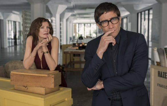 Rene Russo and Jake Gyllenhaal stand looking curiously toward the camera in an art gallery office in the movie Velvet Buzzsaw