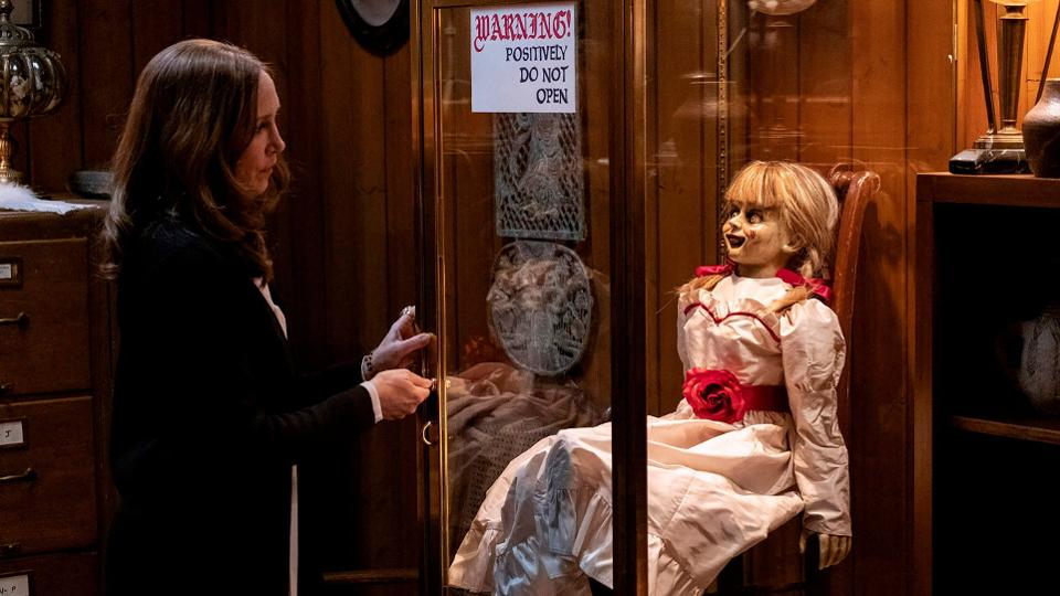 Vera Farmiga locks up Annabelle the doll in a glass cage in the horror movie ANNABELLE COMES HOME