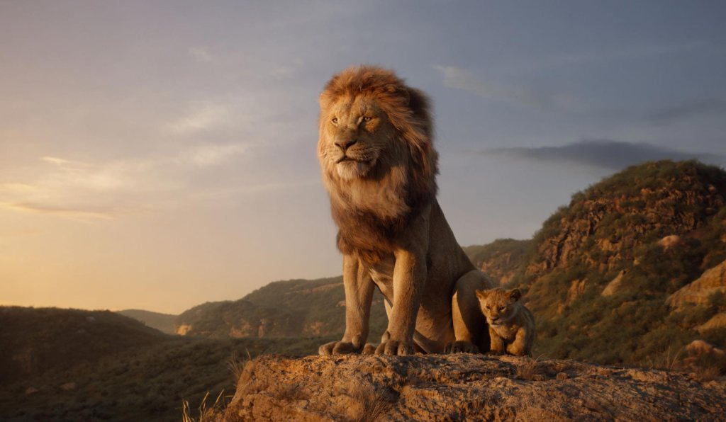 A male lion standing on a hilltop majestically with a lion cub in the 2019 movie The Lion King