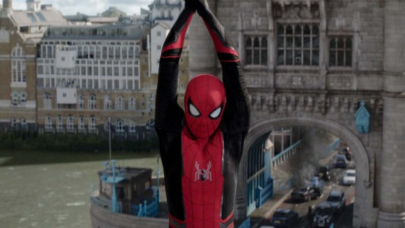 Spiderman swings at the camera holding a web with both hands over his head in the movie Spider-Man: Far From Home