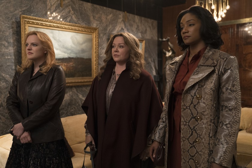 Elisabeth Moss, Melissa McCarthy, and Tiffany Haddish stand seriously in the movie The Kitchen