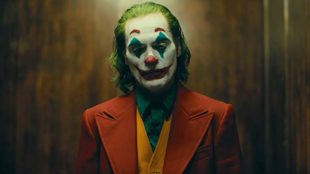 Joaquin Phoenix in the movie Joker wearing his makeup in a suit pondering something in an elevator