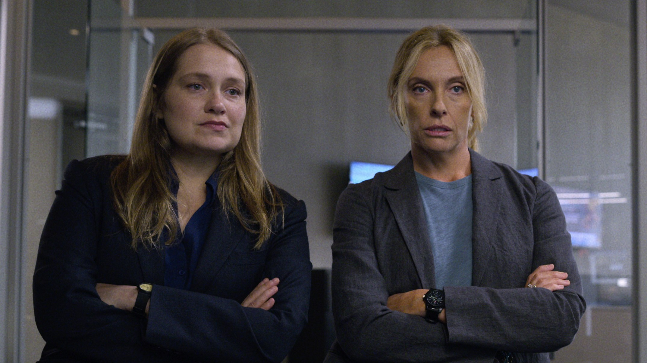 Merritt Wever and Toni Collette sand with their arms crossed observing something in the Netflix show Unbelievable