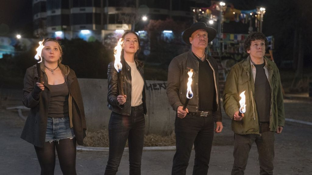 Abigail Breslin, Emma Stone, Woody Harrelson, and Jesse Eisenberg hold torches while looking up in Zombieland: Double Tap