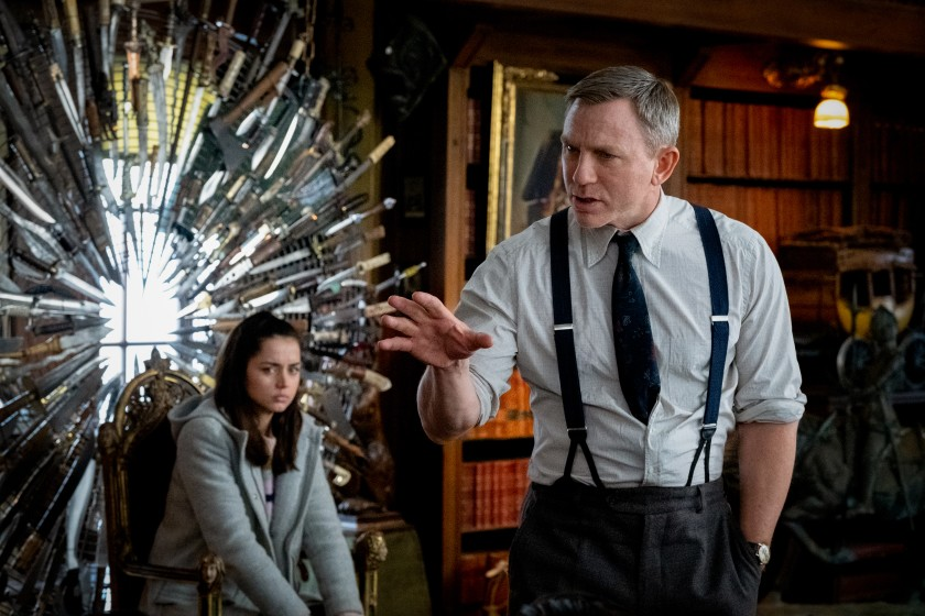Daniel Craig gestures with his hand laying out his theory while Ana de Armas sits by a throne of knives in the movie Knives Out.
