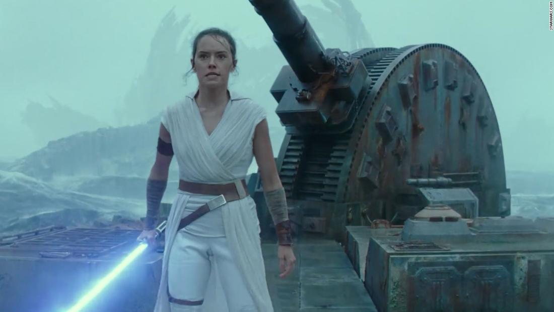 Rey holds her lightsaber by her side while she looks aggressively ahead in the movie Star Wars: The Rise of Skywalker