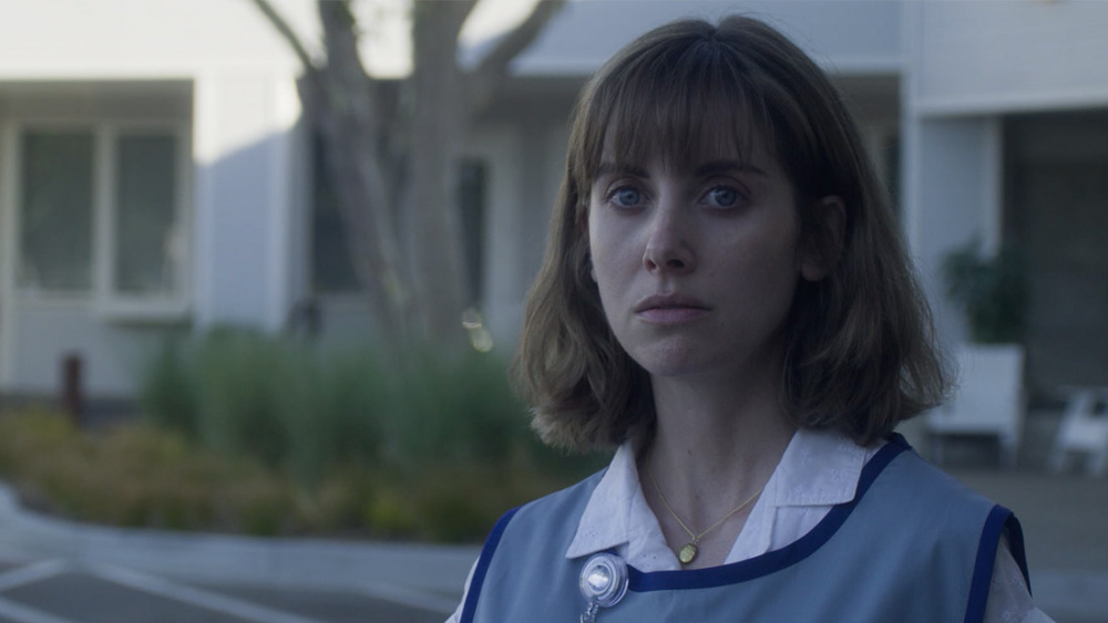 Alison Brie looking sad wearing a craft store smock in the movie Horse Girl
