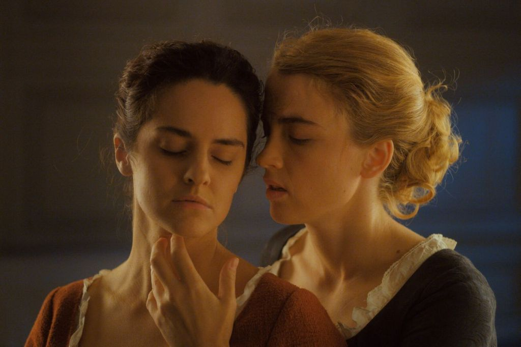Noémie Merlant and Adèle Haenel stand longingly with each other in the movie PORTRAIT OF A LADY ON FIRE