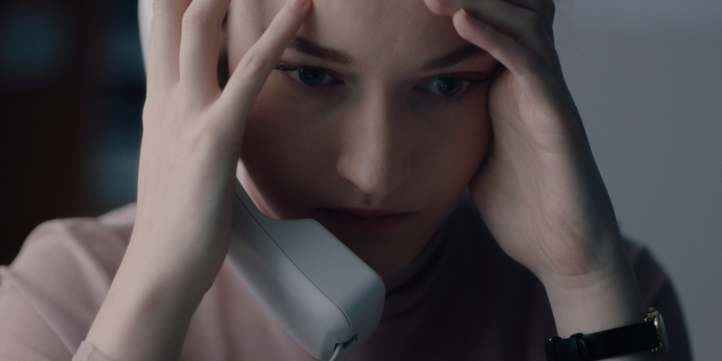 Julia Garner holds her head in her hands while she's on the phone in the movie The Assistant