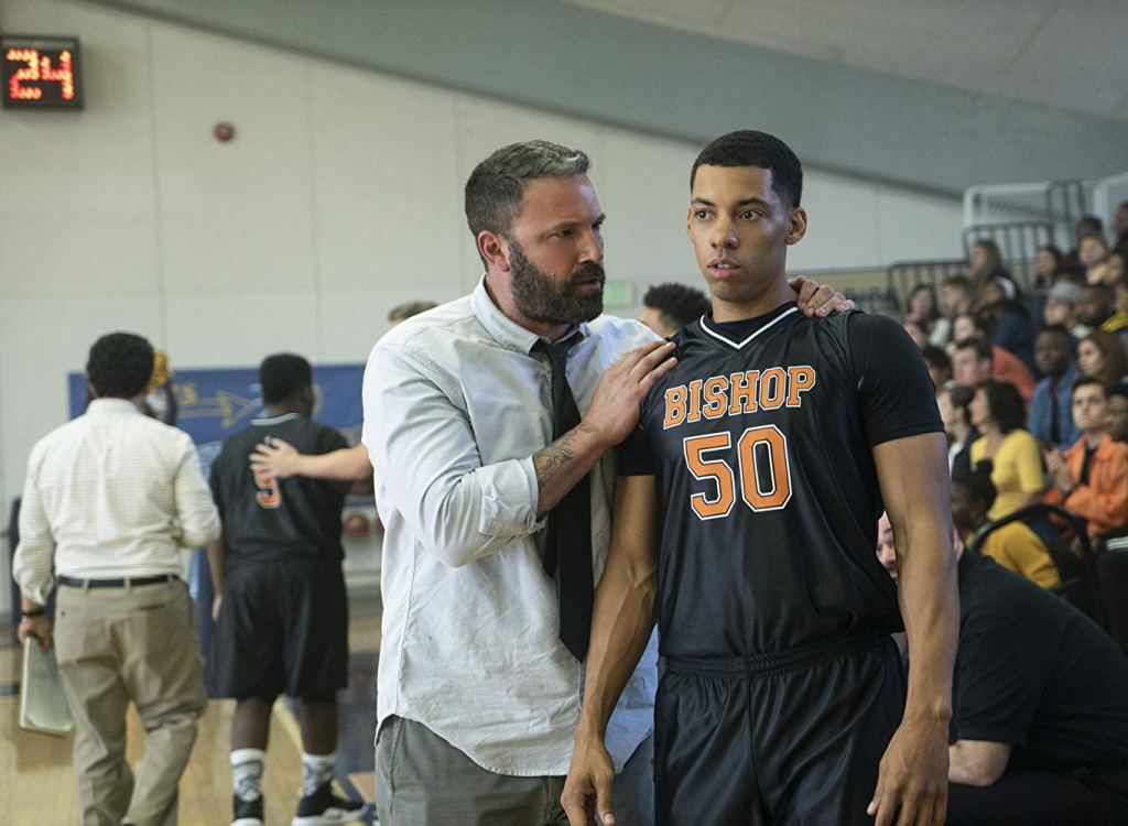 Ben Affleck stands with his hands on a basketball player's shoulders giving advice in the movie The Way Back