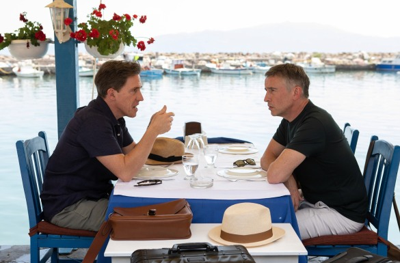 Rob Brydon and Steve Coogan at a restaurant table by the water talking to each other in the film The Trip to Greece