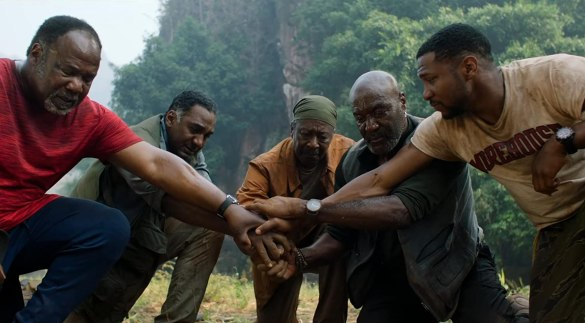 Delroy Lindo, Norm Lewis, Clarke Peters, Isiah Whitlock Jr., and Jonathan Majors in Da 5 Bloods crouch down and bring their hands together in the film Da 5 Bloods
