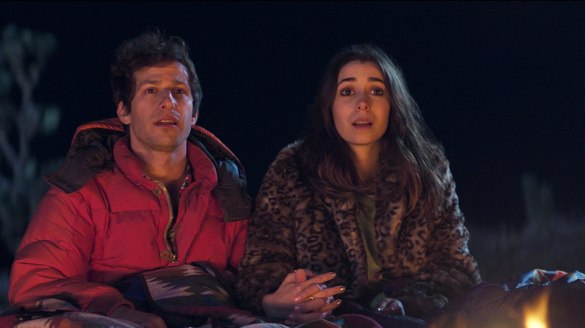 Andy Samberg and Cristin Milioti hold hands looking hopeful by a campfire in the movie Palm Springs