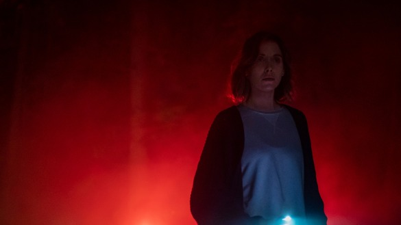 Alison Brie stands against red fog holding her cellphone light in the movie The Rental